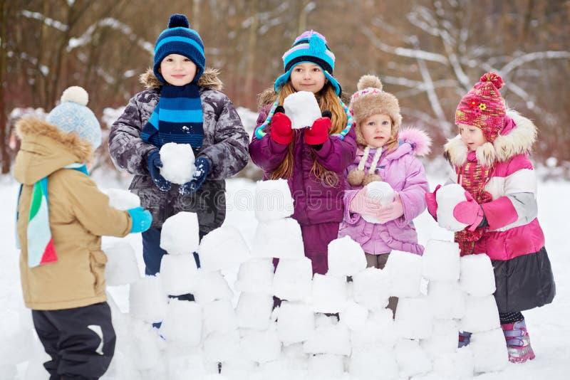 Mur de construction de cinq enfants des briques de neige image stock