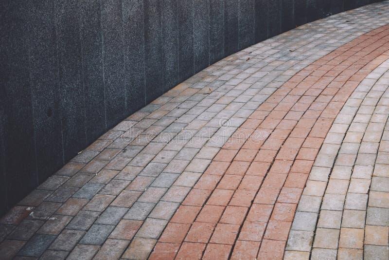 Mur de granit d'une forme grise ronde avec un trottoir de structure et de trottoir, tuile, qui est garnie de l'arc images stock