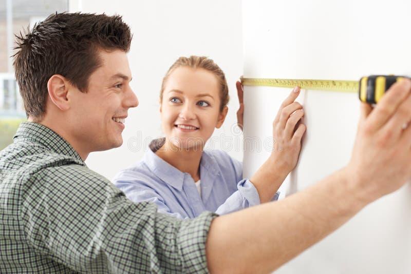Mur de mesure de jeunes couples dans la nouvelle maison photo libre de droits