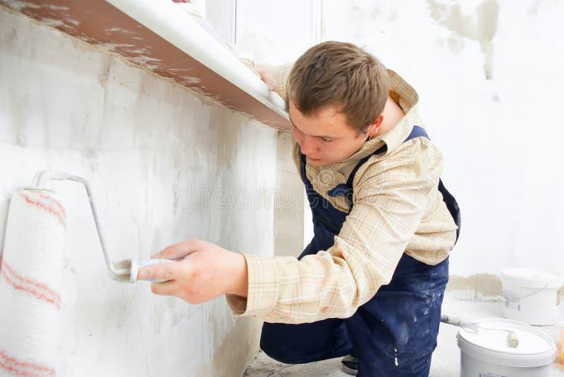 Mur de peinture d'ouvrier avec le rouleau photos stock
