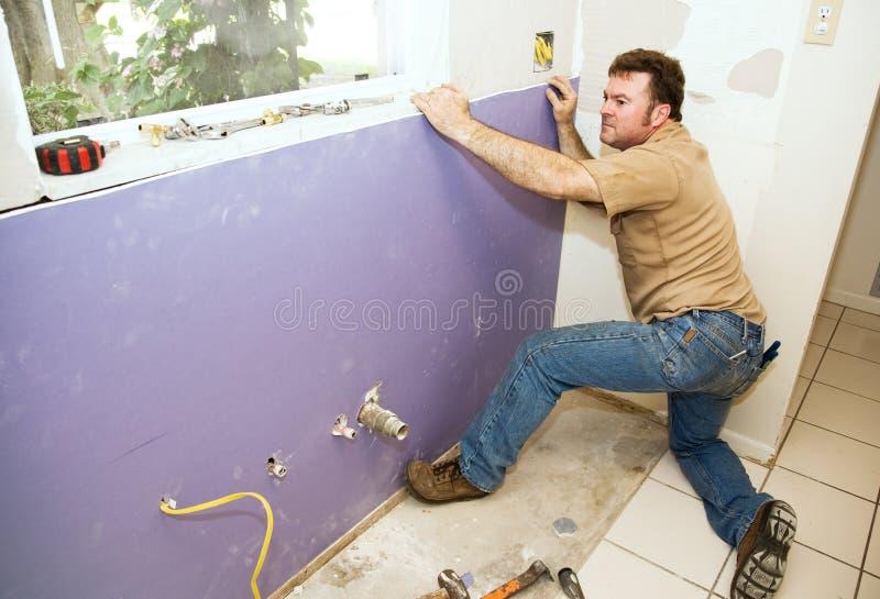 mur de pierres sèches installant l'ouvrier image stock