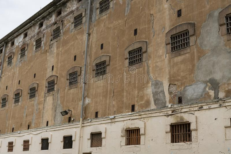 Mur du bâtiment de prison avec des fenêtres des cellules de pricon avec des barres photo stock