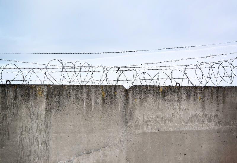 Mur en béton, contre le contexte du barbelé, le concept photographie stock libre de droits