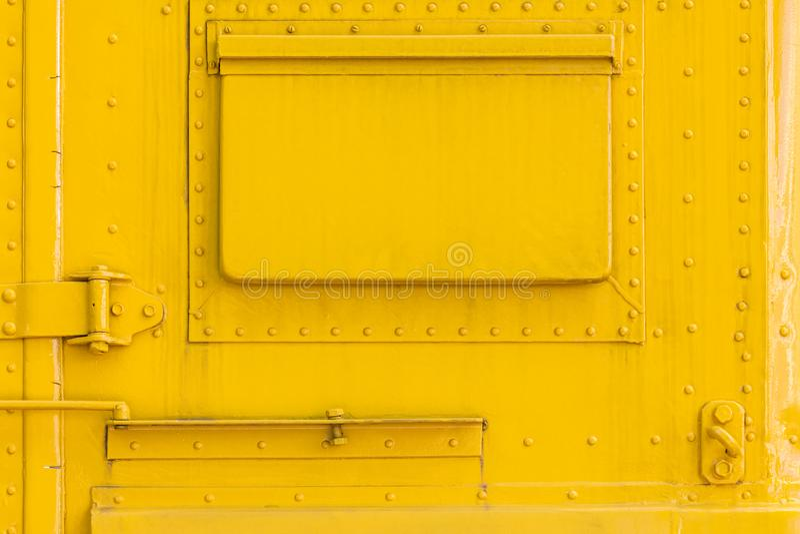 Mur en métal jaune avec la trappe et les rivets fermés photographie stock libre de droits