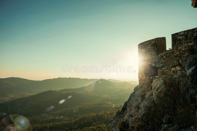 Mur en pierre avec des merlons dans le château au-dessus de la colline sur le crépuscule photographie stock libre de droits