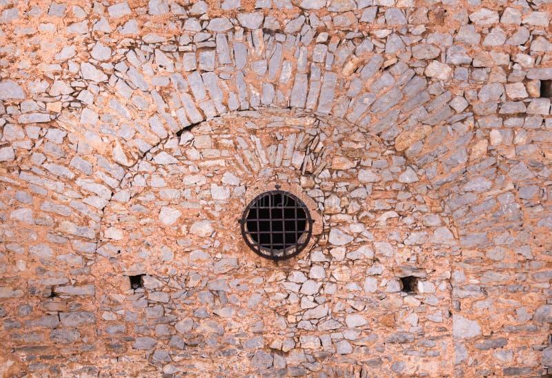 Mur en pierre avec les barres rondes de fenêtre et en métal, d'une forteresse antique photos stock