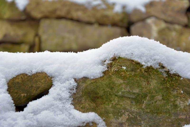Mur en pierre de Milou Pierres couvertes de neige photographie stock