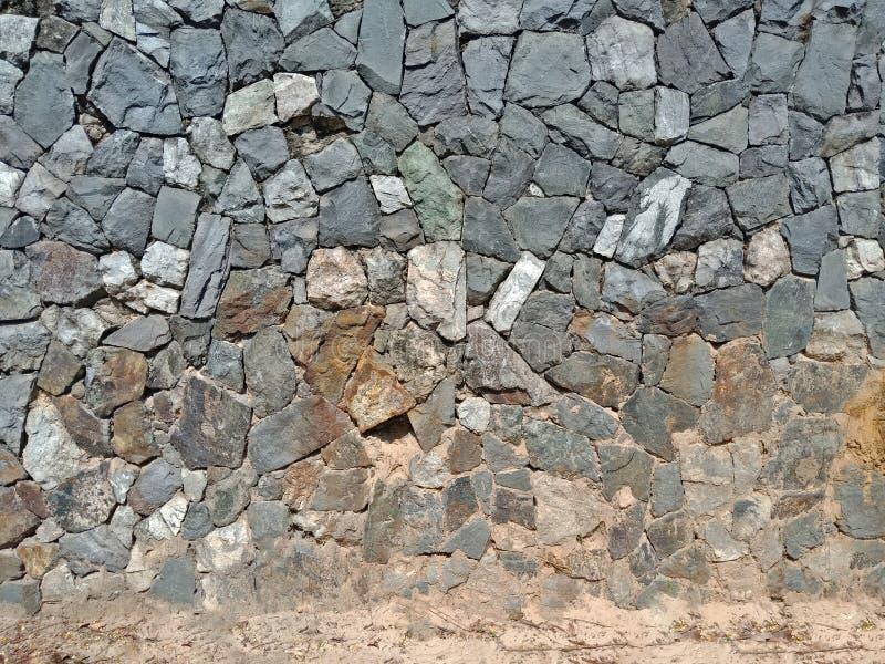 Mur en pierre de mosaïque sale et plancher de sable photographie stock