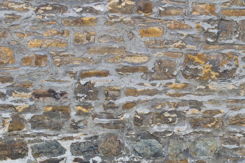 Mur en pierre de vieux sable irrégulier avec des couleurs variables image stock