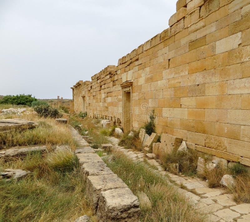 Mur en pierre et blocs aux ruines romaines antiques de Leptis Magna sur la côte méditerranéenne du ` s de la Libye photographie stock libre de droits