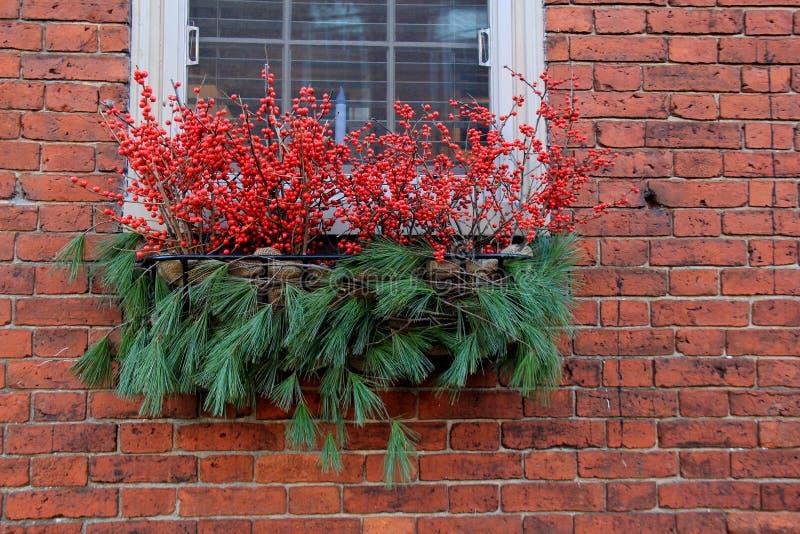 Mur extérieur de jolie brique de maison de pays, avec la boîte de fenêtre remplie d'acclamation de Noël photographie stock libre de droits