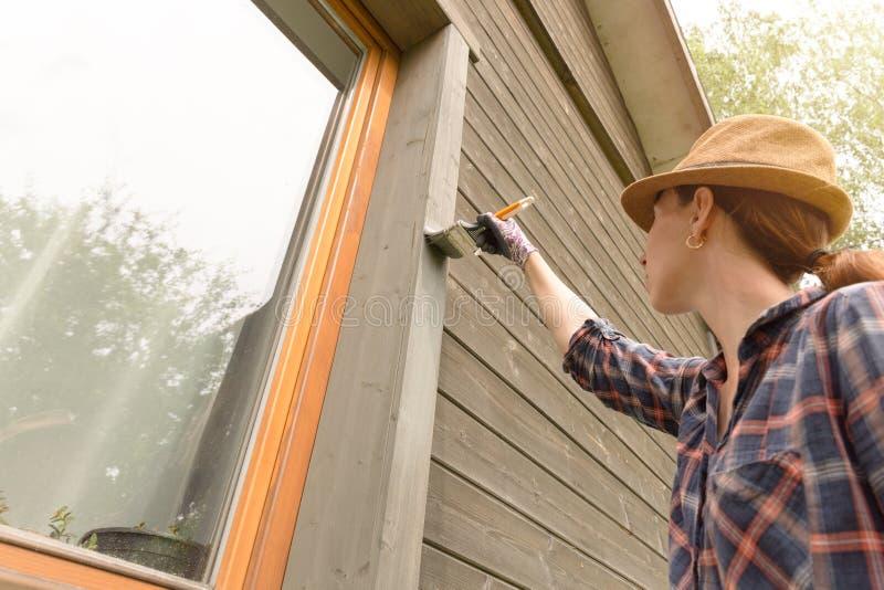 Mur extérieur de maison en bois de peinture de travailleuse avec le pinceau et la couleur protectrice en bois image libre de droits