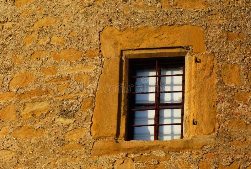 Mur extérieur en pierre ancienne couleur jaune et fenêtre en bois marron images stock