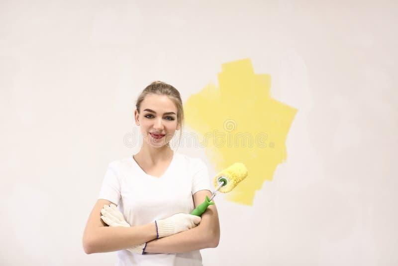 Mur femelle de peinture de décorateur avec le rouleau à l'intérieur photo stock