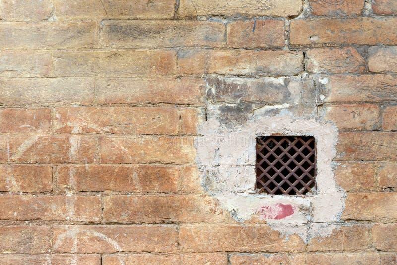 Mur grunge avec une fenêtre avec la grille rouillée de fer image libre de droits
