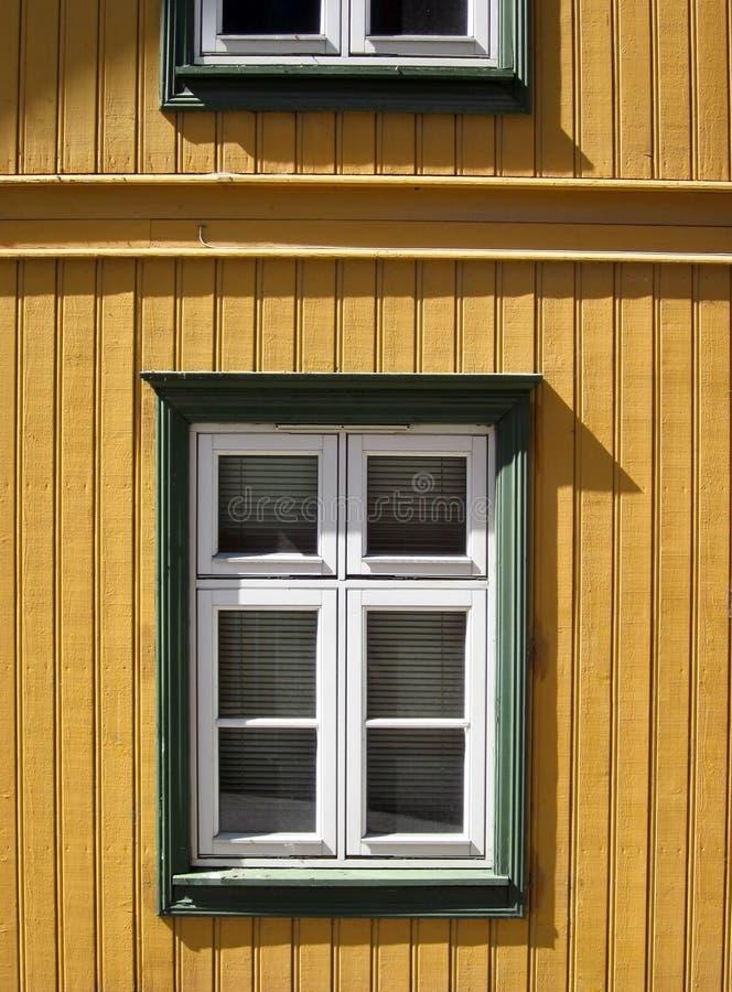 Mur jaune de langue et de cannelure et fenêtres blanches avec le cadre vert photo libre de droits