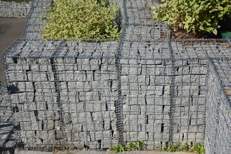 Mur moderne de barri?re de gabion avec des pierres dans le grillage dans la conception de jardin Grillage de Gabion cl?turant ave photos libres de droits