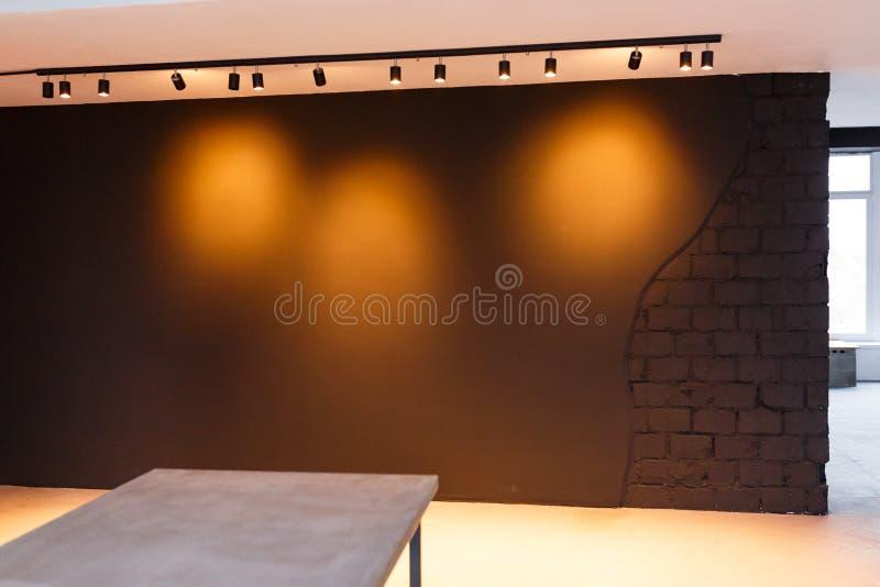 Mur noir de bureau avec la lumière de tache dessus Style de grenier Table concrète dans l'avant photographie stock libre de droits