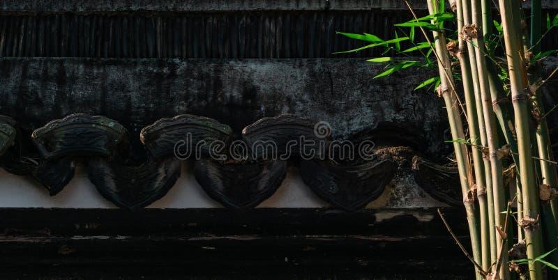 Mur noir de vieille texture chinoise avec les usines en bambou dans le jardin chinois, jardin avec le fond de construction antiqu images libres de droits