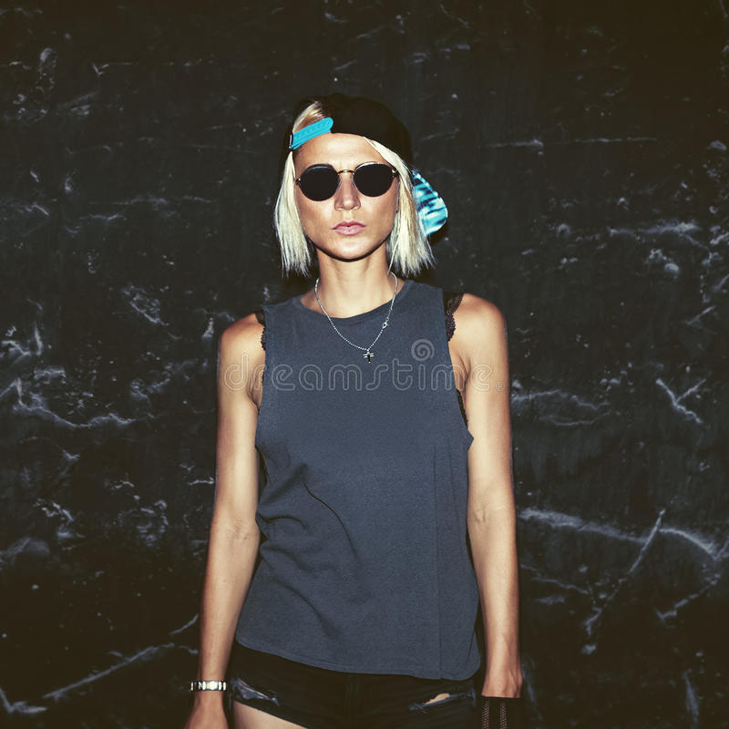 Mur noir proche modèle élégant dans des verres à la mode et un chapeau photos libres de droits