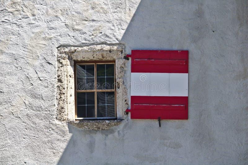 Mur plâtré rugueux de château avec la fenêtre et les volets en bois colorés comme le drapeau autrichien, en partie à la nuance photos libres de droits