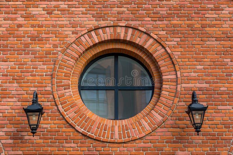Mur rénové d'une vieille usine de textile avec la fenêtre ronde et deux lanternes images libres de droits
