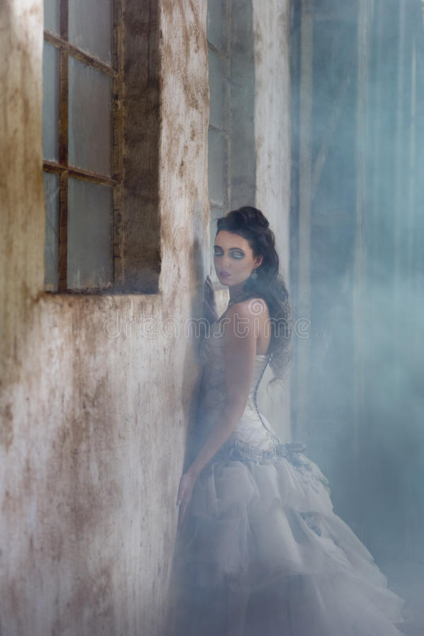 Mur rustique de penchement d'agaisnt de jeune mariée sexy d'imagination entouré par le brouillard photographie stock