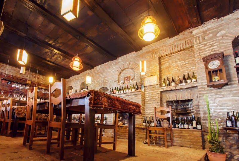 Mura di mattoni di vecchio ristorante con le bottiglie di vino sugli scaffali, sulle tavole di legno e sulle lampade luminose fotografia stock libera da diritti