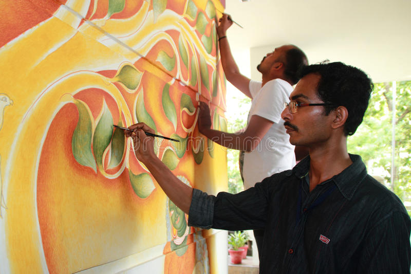 Mural artist. Jayakrishnan paints on the wall during the International Mural painters camp organized by Cultural Department of Kerala on May 18,2013 in Kottayam royalty free stock image