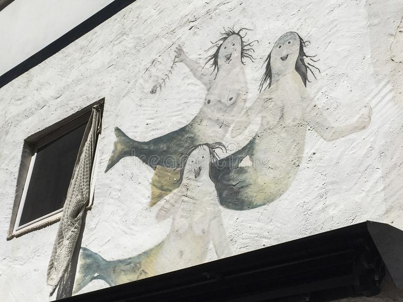 Three mermaids on a white wall royalty free stock photography