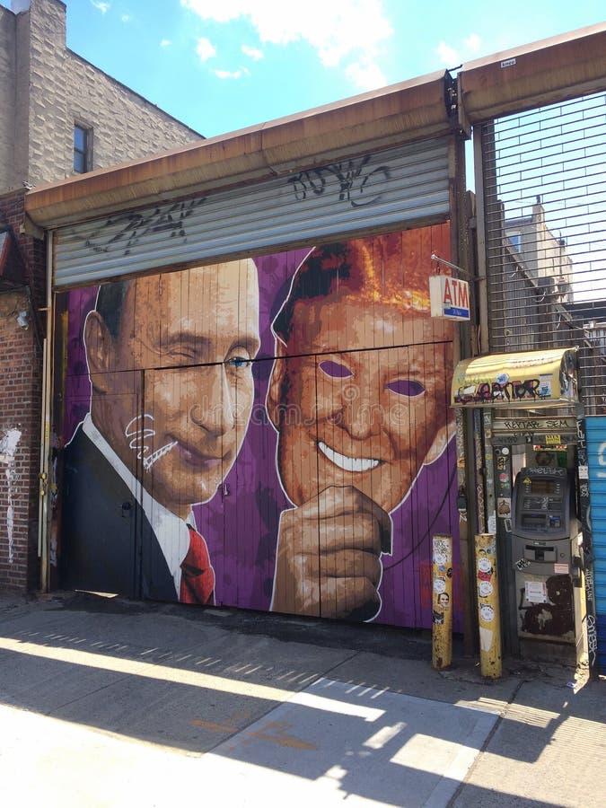 Murale di Putin che tiene una maschera di Donald Trump immagini stock