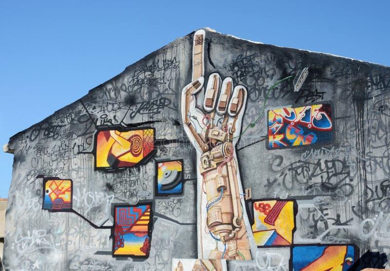 Murales del arte de la pintada de la calle que representan (máquina) el brazo humano artificial en el viejo centro de Paphos, Chi imagen de archivo libre de regalías