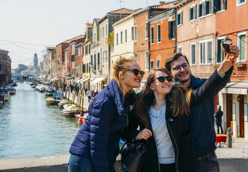 Two young women and man capture a happy selfie on a bridge in Murano near Venice, Italy royalty free stock photo