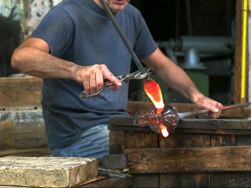 Murano master glass blower adding handles to a vase. Venetian master glass blower adds handles to a vase on the island of murano stock photo