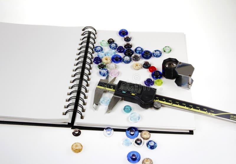 Murano szklani koraliki rozprasza na notatniku z białym tłem obrazy stock