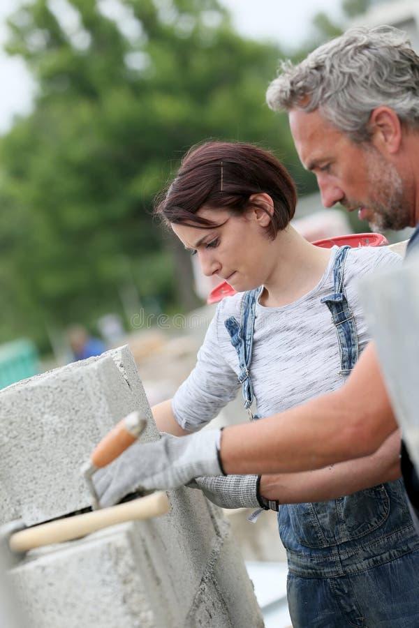 Murare med deltagaren i utbildning för ung kvinna på arbete royaltyfri fotografi