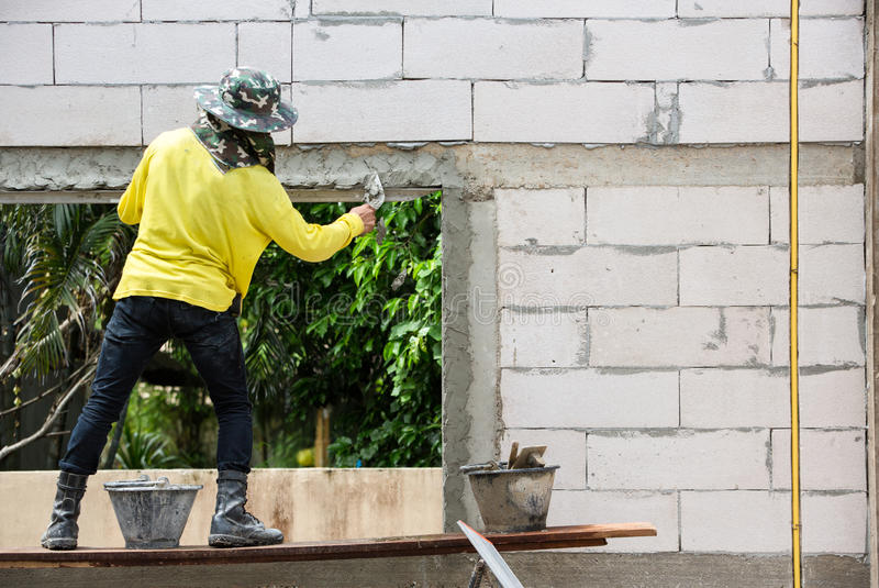 Murare som använder mursleven för att rappa betongen för att bygga väggen, Co royaltyfri fotografi