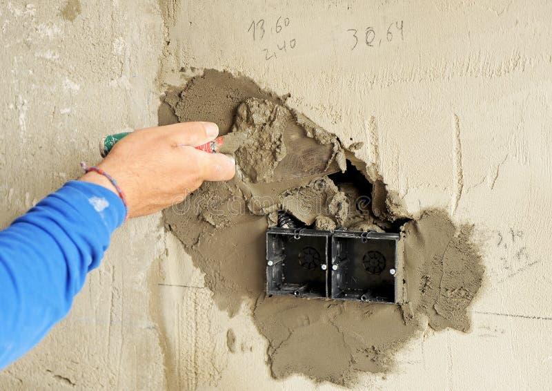 Murare som förlägger en elektrisk ask för elektriska proppar arkivfoton