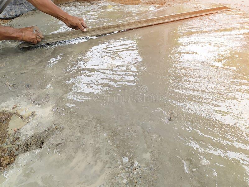 Murarearbetare som jämnar betong med murslevar royaltyfri bild