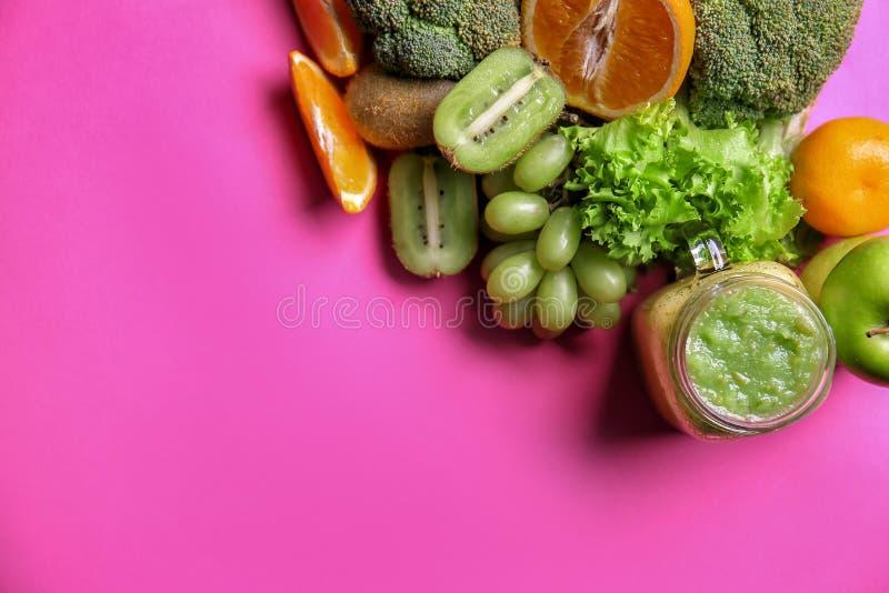 Murarekrus av smaklig grön smoothie och ingredienser på färgbakgrund arkivbild