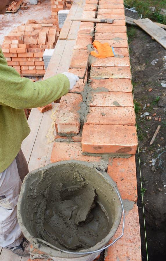 MurareWorker Installing Red kvarter och att dikta tegelstenmurverket fogar ihop den yttre väggen med murslevspackeln arkivbild