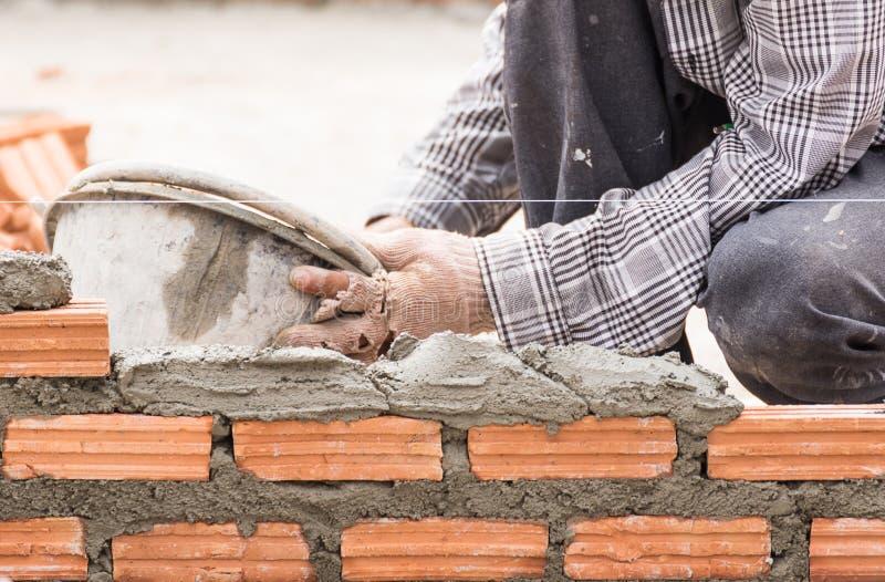 Murarz pracuje w budowie ściana z cegieł zdjęcie stock