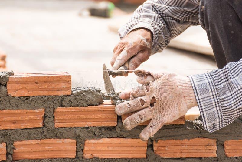 Murarz pracuje w budowie ściana z cegieł obraz stock