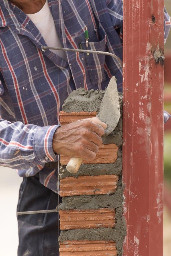 Murarz pracuje w budowie ściana z cegieł zdjęcie royalty free