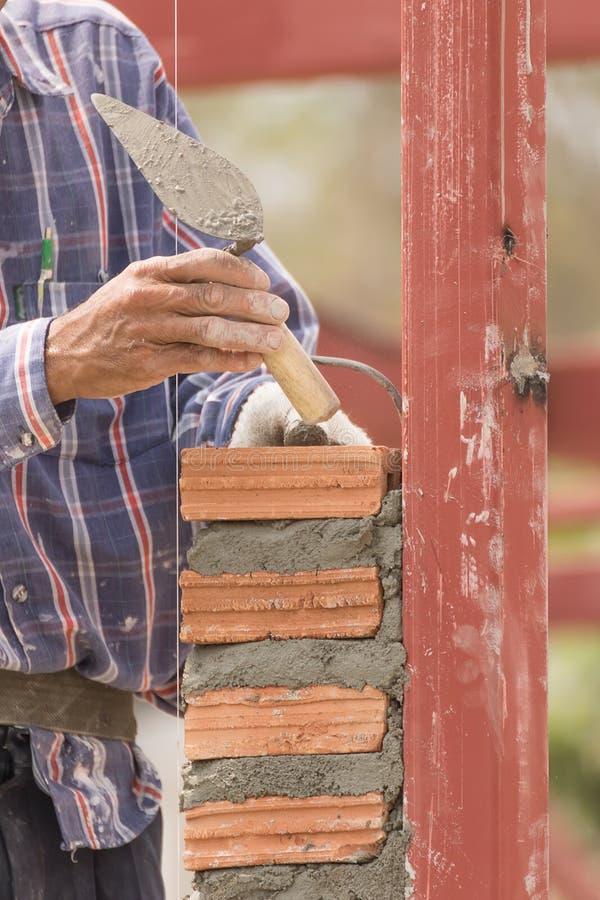 Murarz pracuje w budowie ściana z cegieł obrazy stock