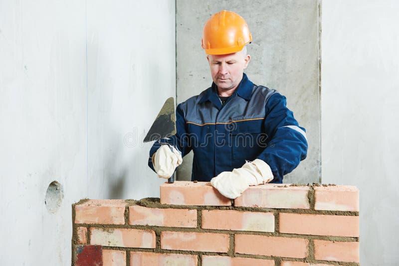 Murarz przy pracą z czerwoną cegłą zdjęcie stock