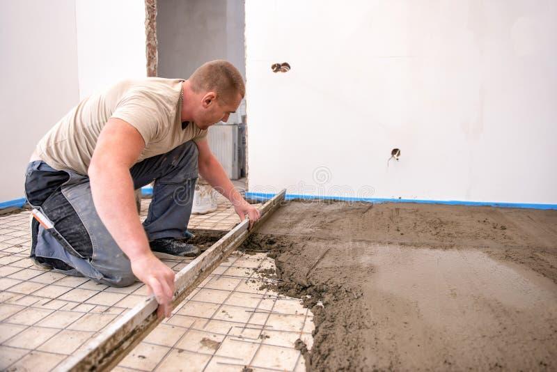 Murarz wyrównuje cementowego screed w niedawno budującym domu fotografia royalty free