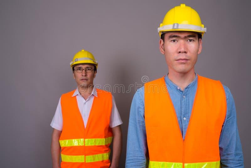 Muratore asiatico di due un giovane uomini insieme contro le sedere grige fotografie stock libere da diritti