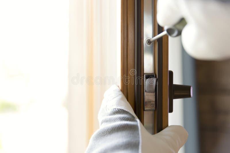 Muratore che installa finestra nella casa Tuttofare che ripara la finestra con il cacciavite immagine stock
