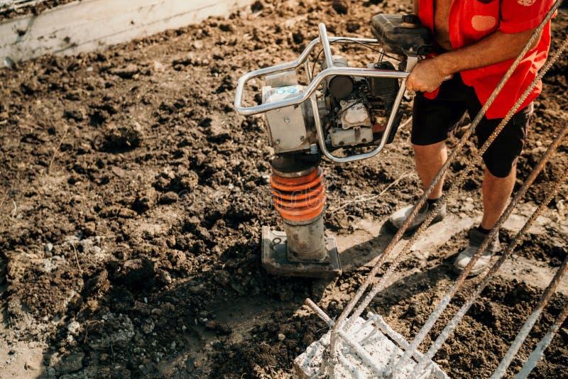 muratore che per mezzo del compattatore per comprimere del suolo e della terra fotografia stock